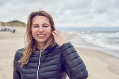 Attractive woman on a windswept beach on a cloudy day. Smiling at the camera as her long hair blows in the breeze royalty free stock photo