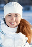 Attractive woman in winter clothing with full guest snow in hands in mittens Royalty Free Stock Photos