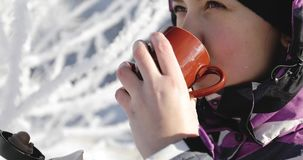 An attractive woman in winter coat drinking coffee from a mug outdoors. A young girl holds a thermos in the hands on background branches in the snow stock video