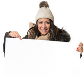 Attractive woman in winter fashion holding a sign. Attractive woman in winter fashion holding a blank white sign Royalty Free Stock Images