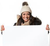 Attractive woman in winter fashion holding a sign. Attractive woman in winter fashion holding a blank white sign Royalty Free Stock Image