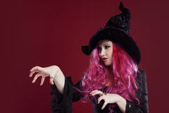 Attractive woman in witches hat and costume with red hair. Halloween Stock Photo