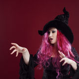 Attractive woman in witches hat and costume with red hair. Halloween Royalty Free Stock Photo