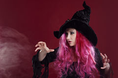 Attractive woman in witches hat and costume with red hair. Halloween Stock Images