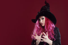 Attractive woman in witches hat and costume with red hair. Halloween Royalty Free Stock Photos