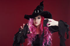 Attractive woman in witches hat and costume with red hair. Halloween Stock Image