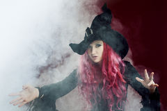 Attractive woman in witches hat with red hair performs magic. Smoke and witchcraft. Attractive woman in witches hat and costume with red hair performs magic on a Royalty Free Stock Photos