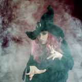 Attractive woman in witches hat with red hair performs magic. Smoke and witchcraft. Attractive woman in witches hat and costume with red hair performs magic on a Stock Image