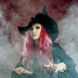 Attractive woman in witches hat with red hair performs magic. Smoke and witchcraft. Attractive woman in witches hat and costume with red hair performs magic on a Royalty Free Stock Photo