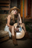 Attractive Woman With Country Look, Indoors Shot, American Country Style. Blonde Girl With Straw Cowboy Hat And Guitar. Fair Hair Royalty Free Stock Image