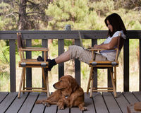 Attractive woman on wooden deck with dog and laptop Stock Photography