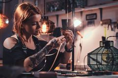 Attractive woman is working at creative glass workshop stock image