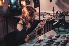 Attractive woman is working at creative glass workshop royalty free stock photography
