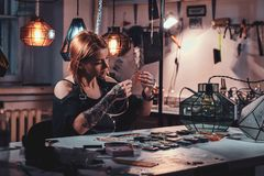 Attractive woman is working at creative glass workshop royalty free stock images