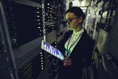 Woman in data centre. Attractive woman is working in data centre with tablet.IT engineer specialist in network server room.Running diagnostics and maintenance royalty free stock image