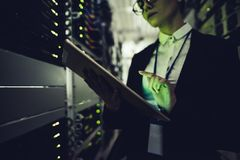 Woman in data centre. Attractive woman is working in data centre with tablet.IT engineer specialist in network server room.Running diagnostics and maintenance stock photo