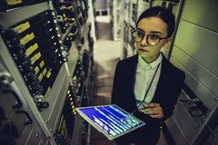 Woman in data centre. Attractive woman is working in data centre with tablet.IT engineer specialist in network server room.Running diagnostics and maintenance stock photos