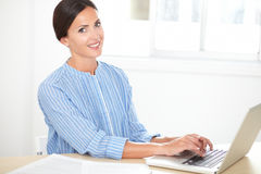 Attractive woman working on her laptop. Attractive woman in stylish blouse working on her laptop at a home room royalty free stock photo