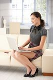 Attractive woman working at home using laptop Stock Photos