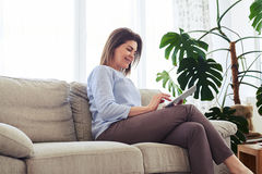 Attractive woman working in laptop while sitting on sofa Royalty Free Stock Photos