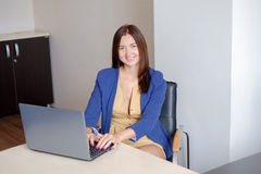 Attractive woman working on laptop in start-up office Royalty Free Stock Photo