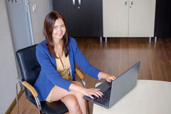 Attractive woman working on laptop in start-up office stock images