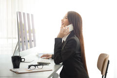 Attractive woman working in office on laptop Stock Photos