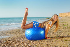 Attractive woman working out on the beach. Beautiful young woman doing fitness exercise on a beach Royalty Free Stock Photos