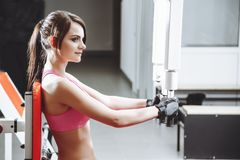 Attractive woman working out on butterfly machine. Young woman bodybuilder doing exercise for chest in the gym. royalty free stock images