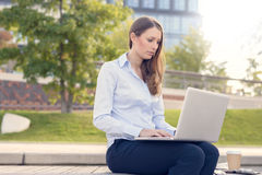 Attractive woman working outdoor on a laptop Royalty Free Stock Images