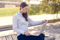 Attractive woman working outdoor on a laptop Royalty Free Stock Image