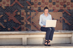Attractive woman working outdoor on a laptop Royalty Free Stock Photography