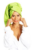 Attractive woman wrapped in towel, holding her mouth in a smile. Stock Photo
