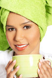 Attractive woman wrapped in towel with turban on head, holding a Royalty Free Stock Photo
