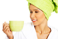 Attractive woman wrapped in towel with turban on head, holding a Stock Photo