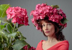 Attractive woman in wreath with coral hydrangea blossoms royalty free stock image