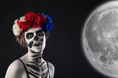 Attractive woman in a wreath with sugar skull make-up stock image