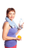 Attractive woman 50 years with an orange and a bottle of water Stock Images