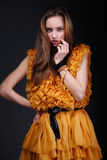 Attractive woman in yellow dress with hand near her face Stock Photography