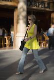 Attractive woman in yellow dress walking on Passeig de Gr�cia in the Eixample district, busy street in Barcelona, Spain, Europe Stock Photo