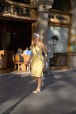 Attractive woman in yellow dress walking on Passeig de Gr�cia in the Eixample district, busy street in Barcelona, Spain, Europe Royalty Free Stock Photos