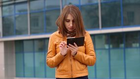 Attractive woman in yellow jacket using mobile phone outdoor in the city. messaging.  stock video