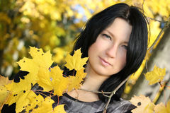 Attractive woman with yellow leafage Royalty Free Stock Photo