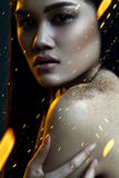 Attractive woman in yellow light under golden rain Royalty Free Stock Photography