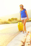 An attractive woman with a yellow suitcase is traveling on the r Stock Image