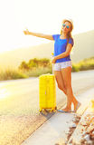 An attractive woman with a yellow suitcase is traveling on the r Royalty Free Stock Image