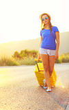 An attractive woman with a yellow suitcase is traveling on the r Royalty Free Stock Images