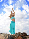 Attractive woman in zen yoga pose at rock mountain top in relax Royalty Free Stock Photos