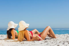 Attractive women in bikinis sunbathing. On the beach royalty free stock images