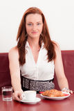 Attractive women with a cappuccino and croissant Royalty Free Stock Images
